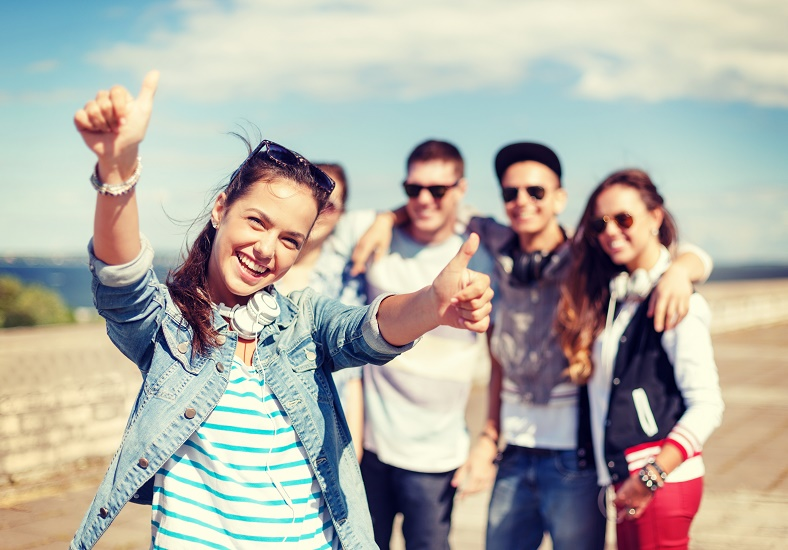 Smiling woman with thumbs up with friends